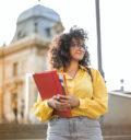 Frau in einer Bluse vor einem Gebäude.